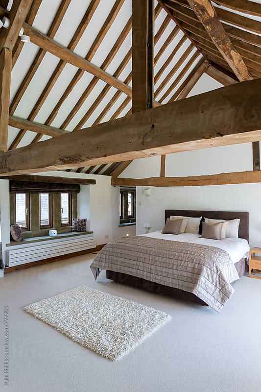 Timber framed bedroom in a converted barn. by Paul Phillips for Stocksy United