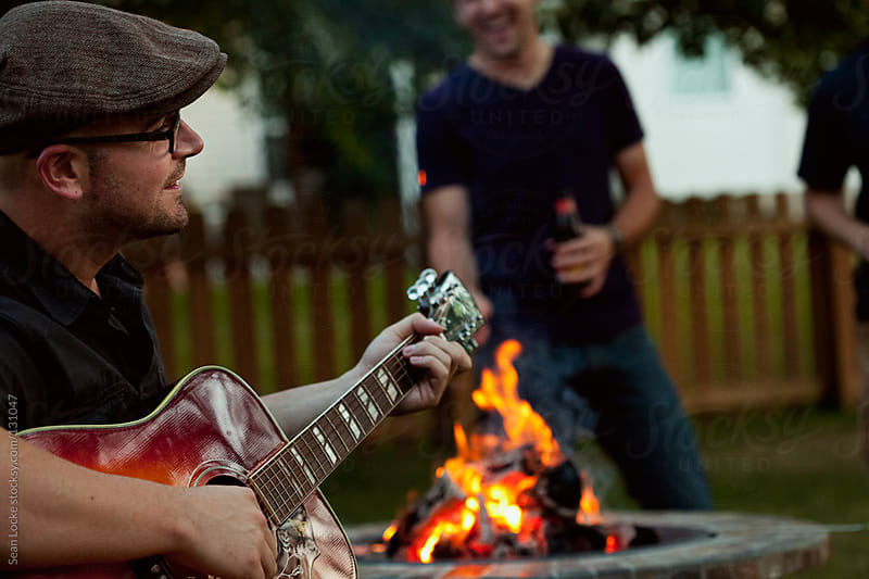 Party: Hipster Playing Guitar By Fire by Sean Locke for Stocksy United