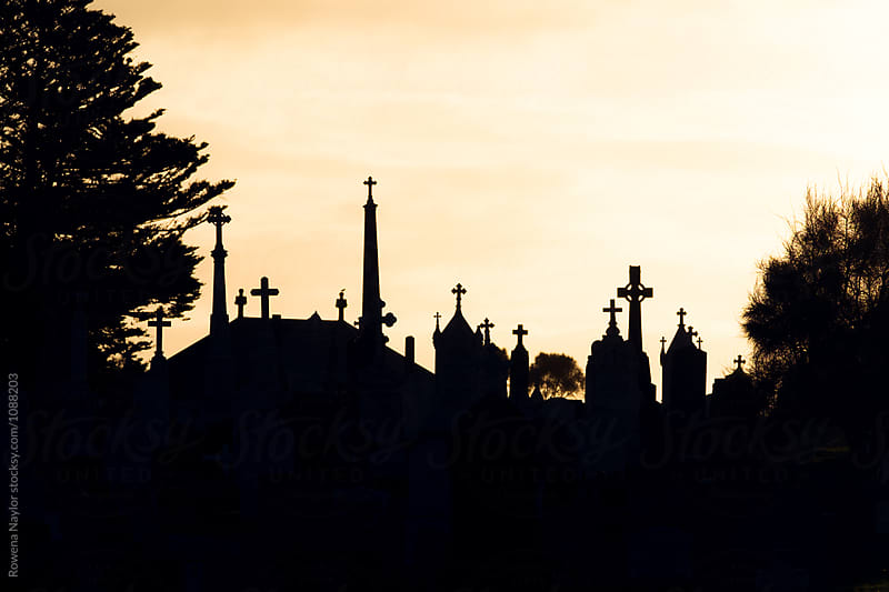 Silouette of catholic gravestones in cemetery