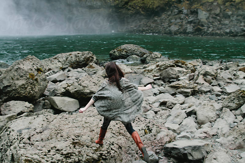 Young woman jumps across rocks by Jesse Morrow for Stocksy United