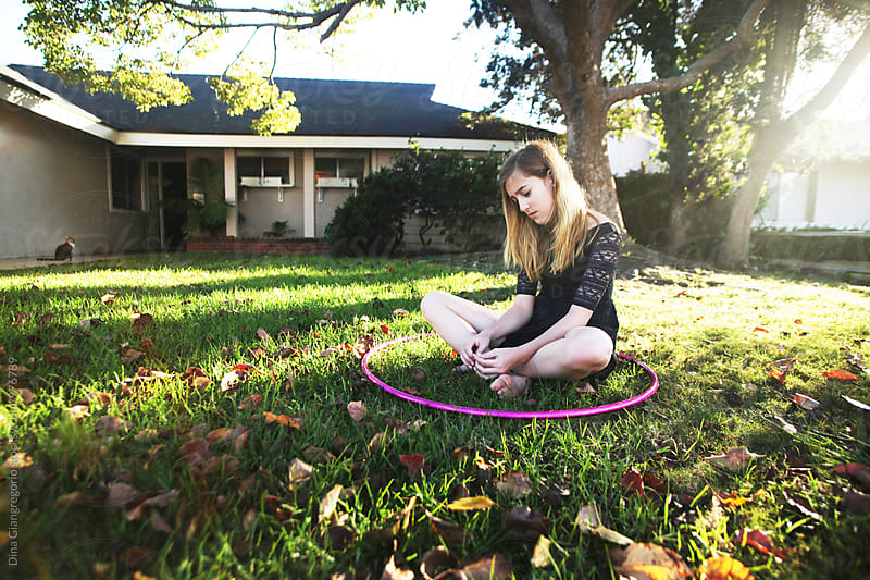 Girl Sitting On Grass in The Middle Of a Hoola Hoop by Dina Giangregorio for Stocksy United