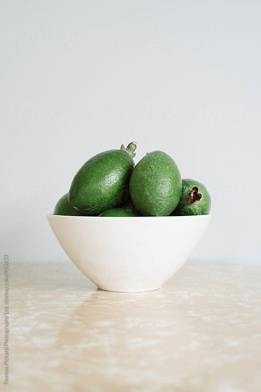 Feijoa fruit in a white bowl on a table, New Zealand. by Thomas Pickard for Stocksy United