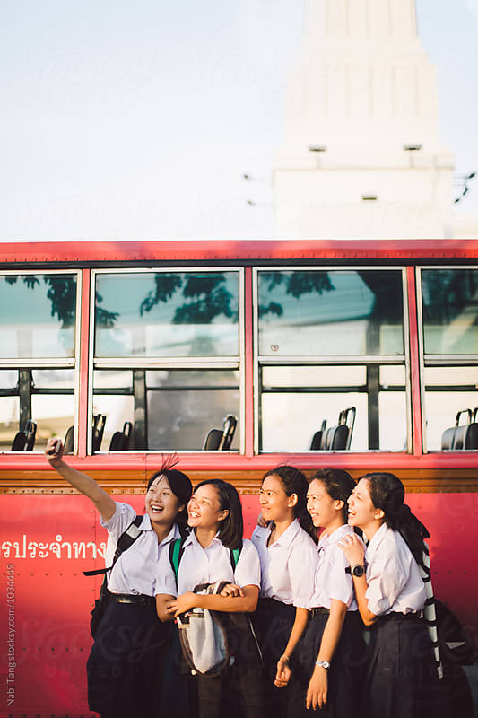 Thai school girl group making selfie together at the bus stop afterschool by Nabi Tang for Stocksy United