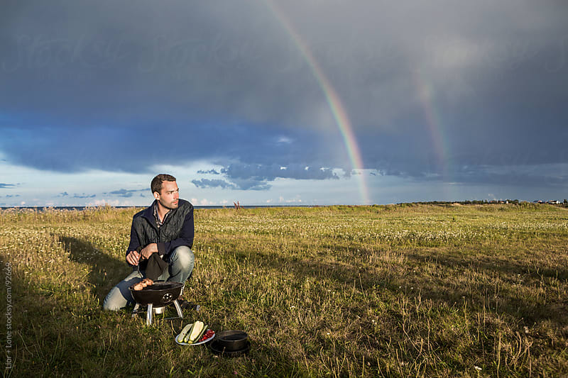 Man barbecuing with rainbow in the background by Lior + Lone for Stocksy United
