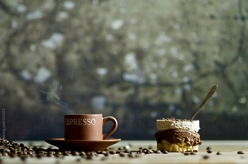 Spilled coffee beans with peace of cake and cup of espresso coffee by Marija Anicic for Stocksy United