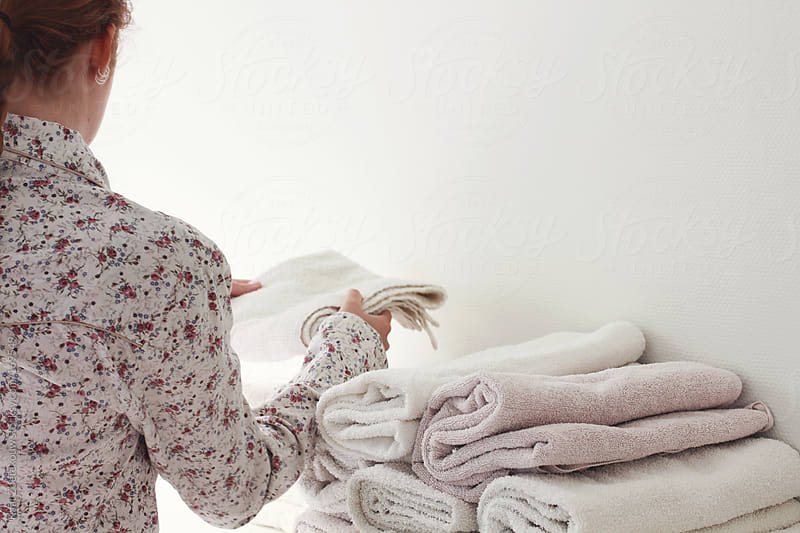 Young red haired woman in laundry room putting away folded towels. by Kaat Zoetekouw for Stocksy United