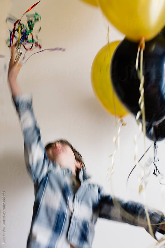 Little boy throwing confetti above his head in front of a white background by Beatrix Boros for Stocksy United