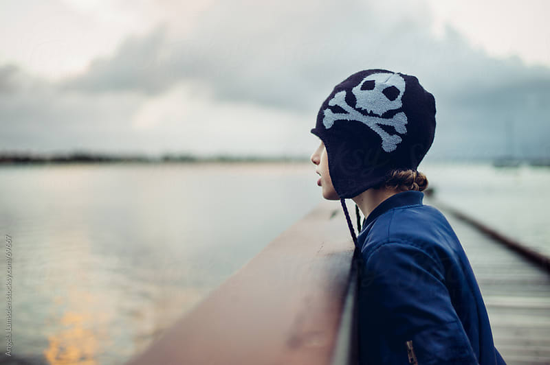 Boy looking out on a river by Angela Lumsden for Stocksy United