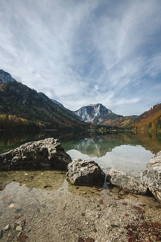 landscape reflecting in a mountain lake in autumn by Leander Nardin for Stocksy United