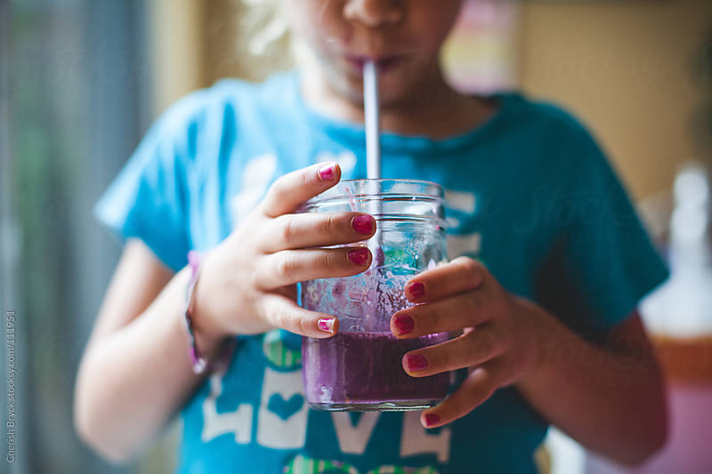 Young girls sips a blueberry smoothie. by Cherish Bryck for Stocksy United