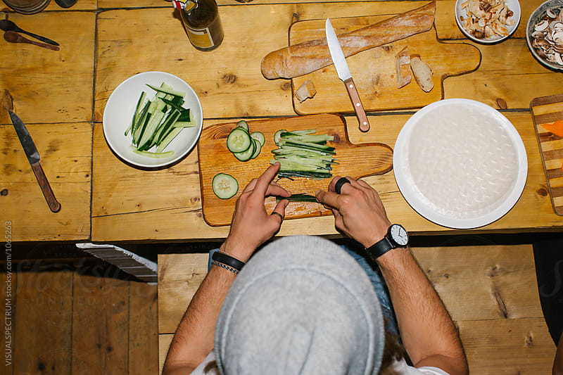Overhead Shot of Young Caucasian Hipster Slicing Cucumber on Rustic Wooden Kitchen Counter by VISUALSPECTRUM for Stocksy United