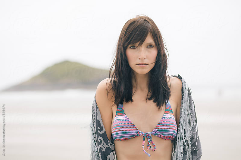 A portrait of a young woman looking into the camera in a pink bikini by Ania Boniecka for Stocksy United