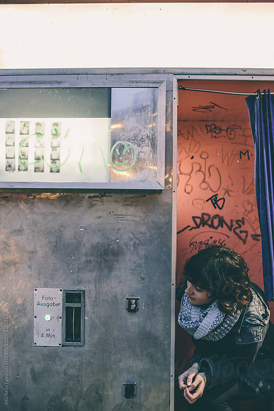 Young woman sitting in a photo booth by michela ravasio for Stocksy United