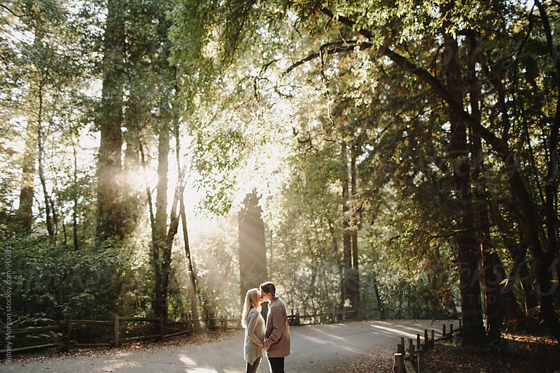 Couple in Front of in Forest with Light Beams Coming In by Sidney Morgan for Stocksy United