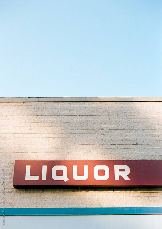 Liqour store sign with dappled lighting by Cameron Whitman for Stocksy United