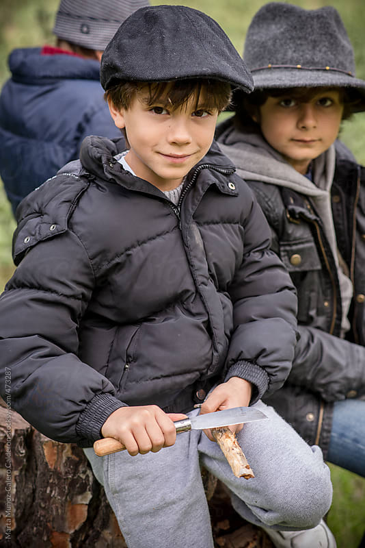 Boys wood carving with pocket knifes in the woods by Marta Muñoz-Calero Calderon for Stocksy United