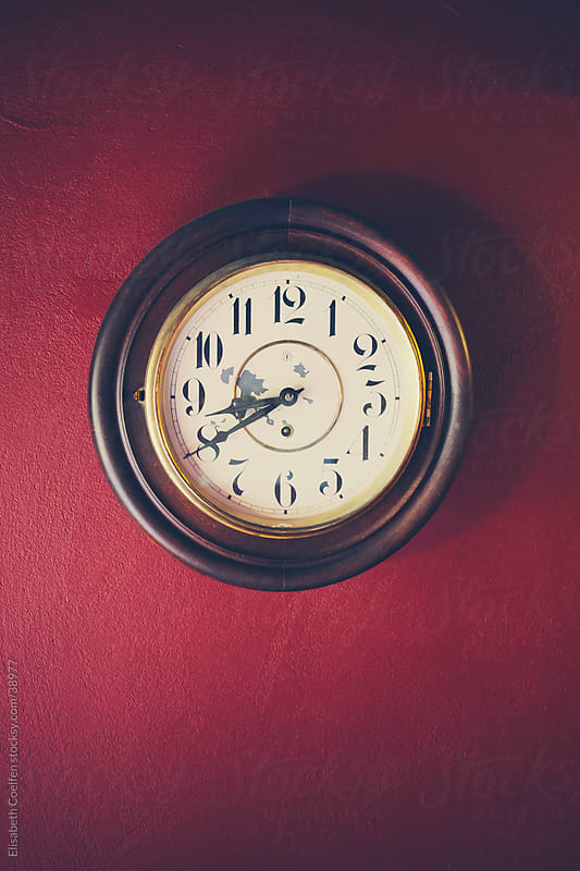 Antique wall clock hanging on a red wall by Elisabeth Coelfen for Stocksy United