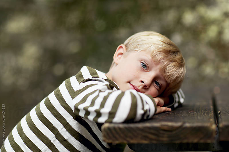 boy resting his head on a table  by Kelly Knox for Stocksy United