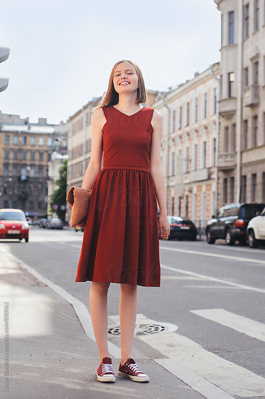 Happy young woman standing at the street by Lyuba Burakova for Stocksy United