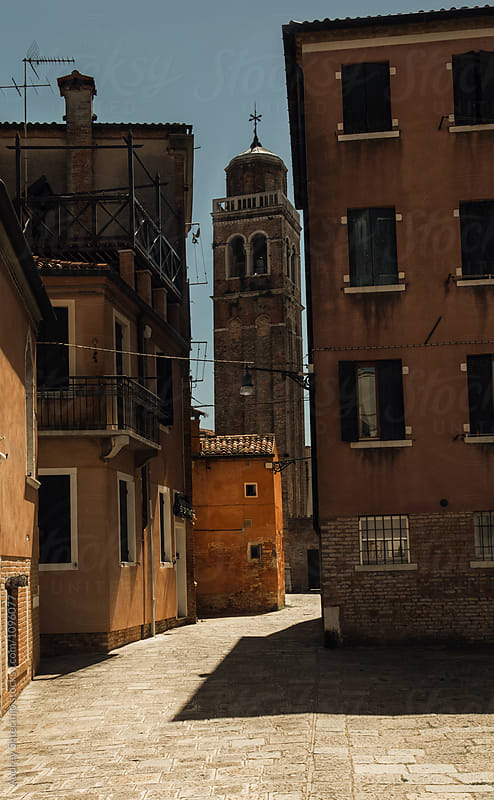 Typical mediterranean street on sunny day with church bell tower.Italy. by Marko Milanovic for Stocksy United