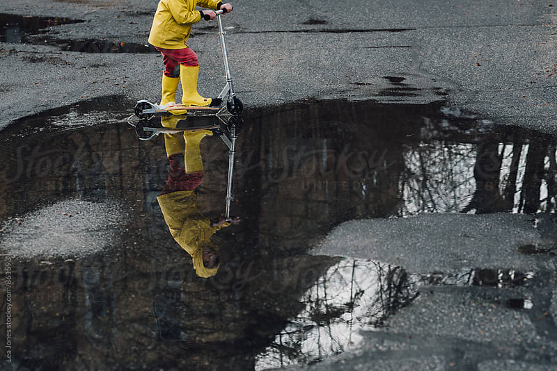 child riding through a puddle with a scooter by Léa Jones for Stocksy United