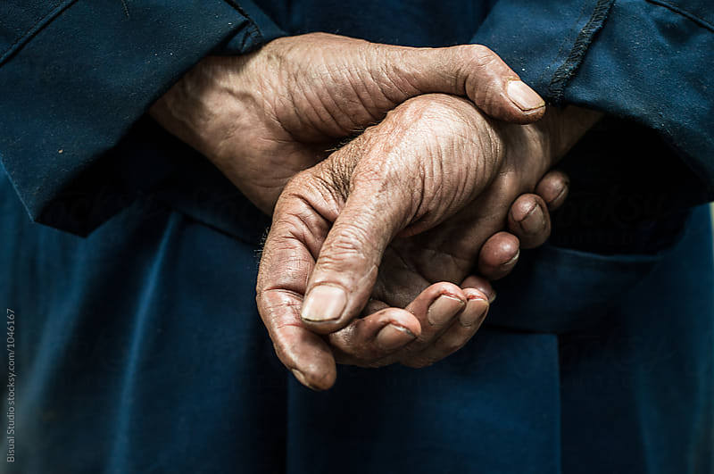 Hands full of grease belonging to a  senior mechanic by Bisual Studio for Stocksy United