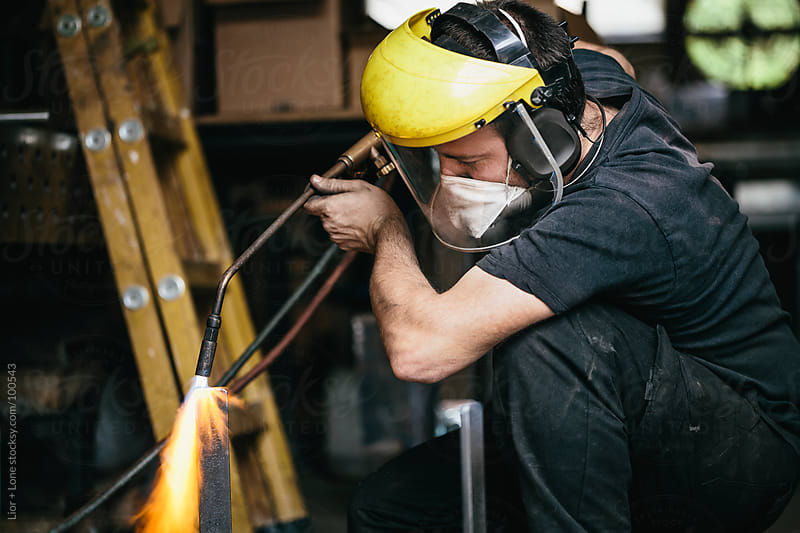Young working man welding metal in workshop by Lior + Lone for Stocksy United