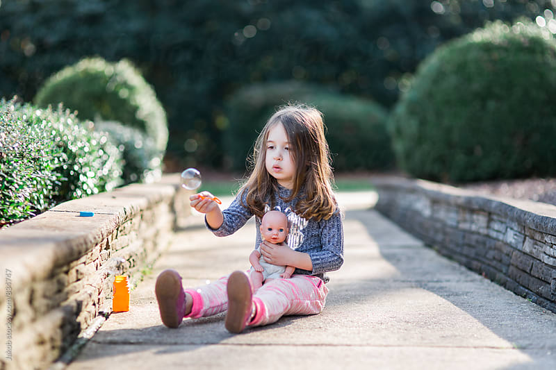 Beautiful young girl sitting on the ground blowing bubbles with her baby doll by Jakob for Stocksy United