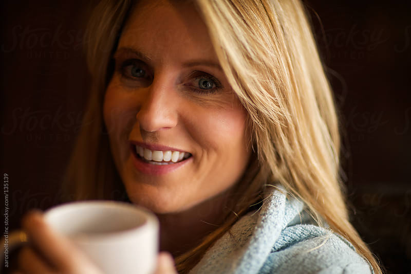 Woman smiling over coffee by aaronbelford inc for Stocksy United