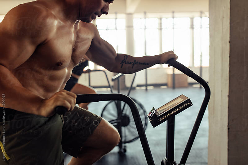 Muscular man at the gym riding on the spinning bike  by Jacob Ammentorp Lund for Stocksy United