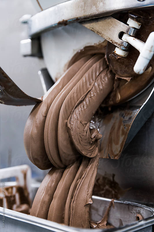 Thick chocolate ice cream coming out from industrial machine by Lior + Lone for Stocksy United