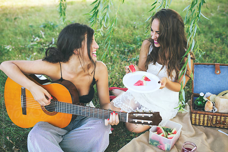Young woman playing guitar for her friends in nature by Jovana Rikalo for Stocksy United