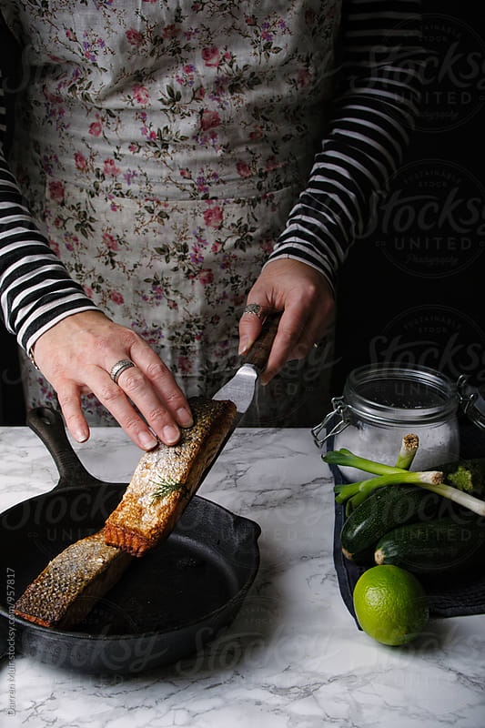 Woman preparing a salmon meal: Woman taking a fillet of roasted salmon from a cast iron skillet. by Darren Muir for Stocksy United
