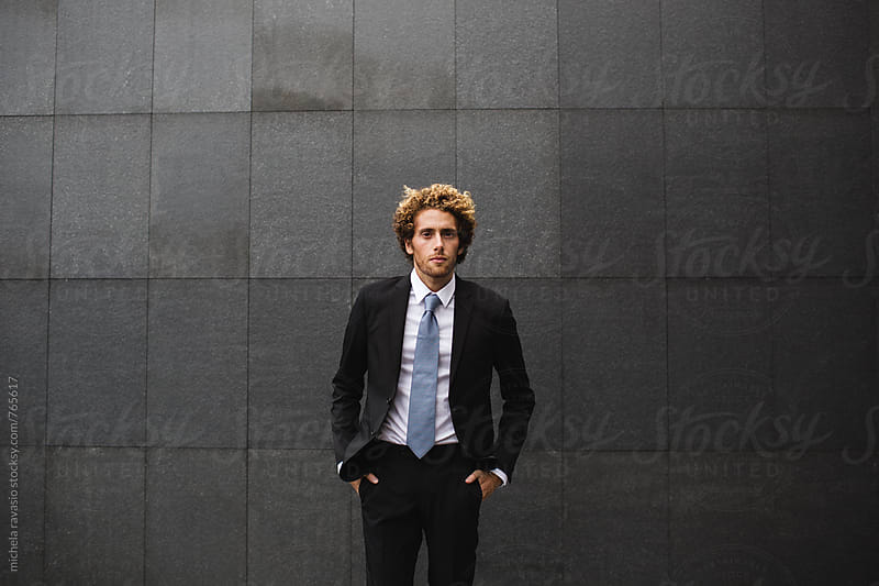 Elegant man dressed in front of a black wall by michela ravasio for Stocksy United