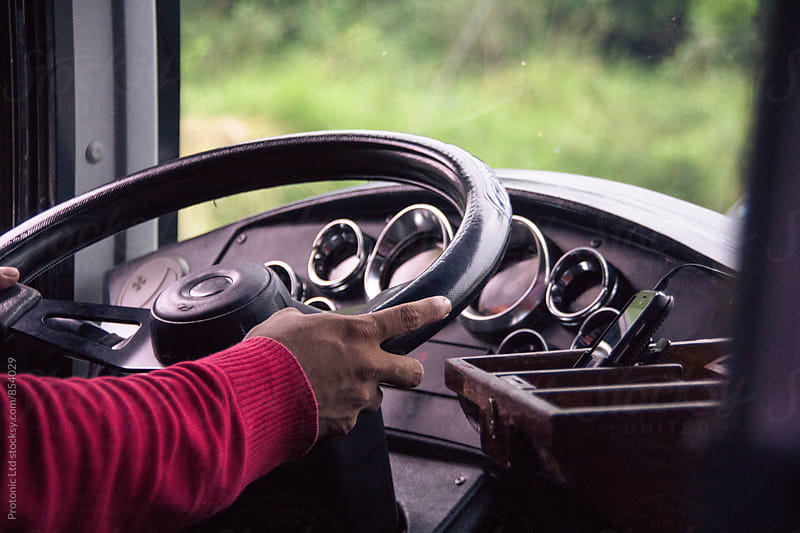 Closeup of bus driver with hands on steering wheel by Per Swantesson for Stocksy United