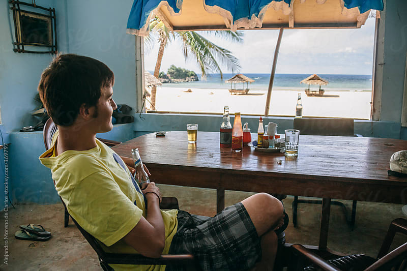 Young man enjoying beer on beach restaurant bar on tropical island by Alejandro Moreno de Carlos for Stocksy United