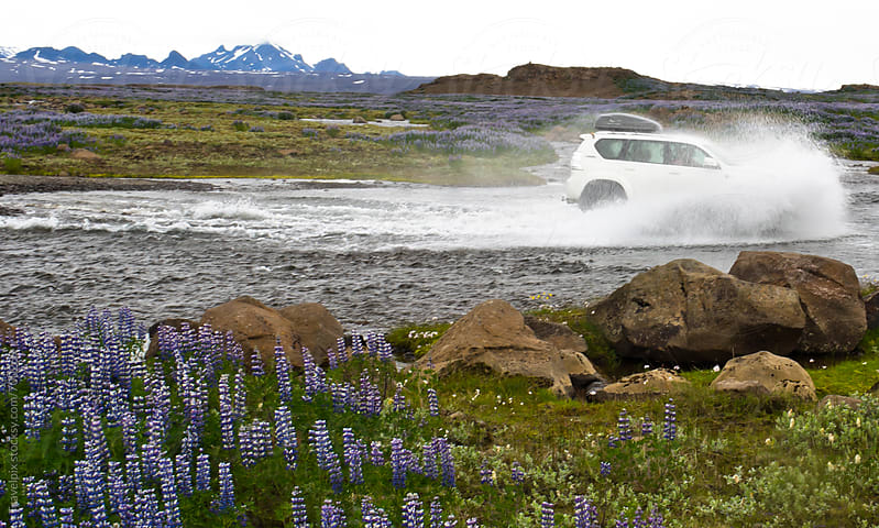 4WD car wades through river in Iceland by Travelpix for Stocksy United