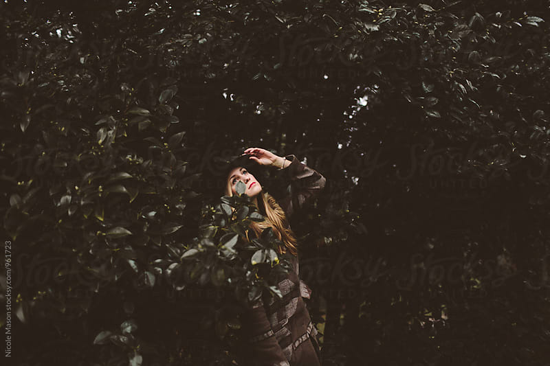 young blonde woman standing against dark shrubs in park by Nicole Mason for Stocksy United