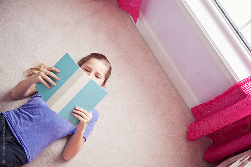 Girl: Lying on the Floor, Reading a Book by Sean Locke for Stocksy United