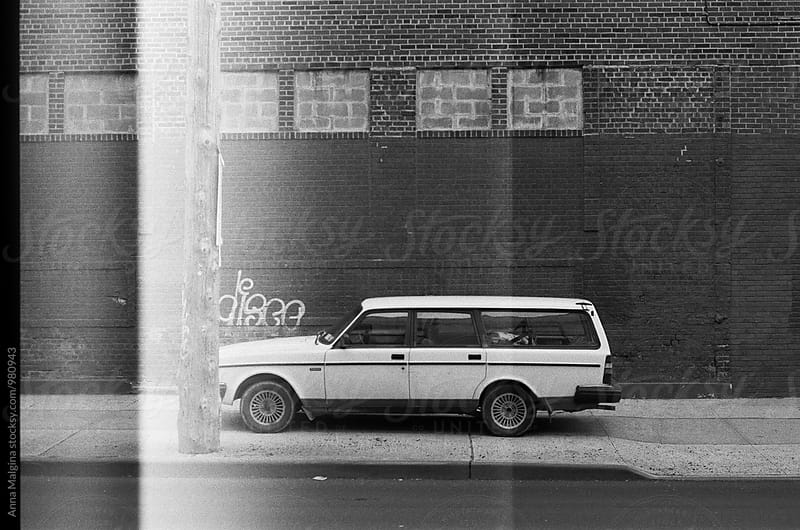 The black and white film photo of white car in New York street by Anna Malgina for Stocksy United