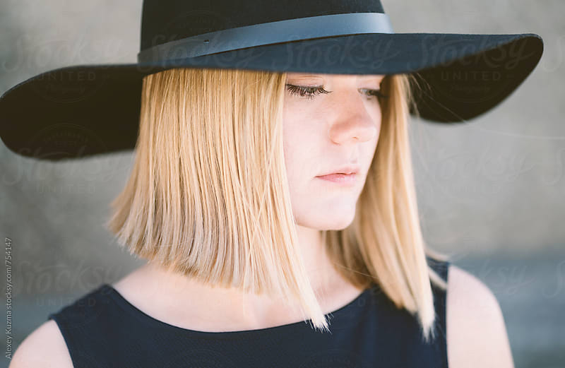 portrait of young blond woman with black hat  by Alexey Kuzma for Stocksy United