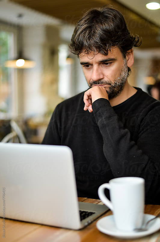 Man working on his laptop at a cafe by Bisual Studio for Stocksy United