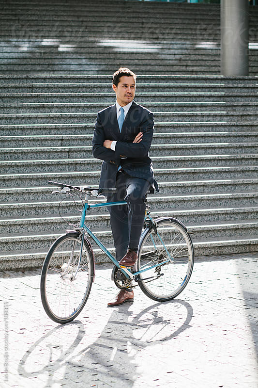 Young business manstanding still with his bike by Ivo de Bruijn for Stocksy United