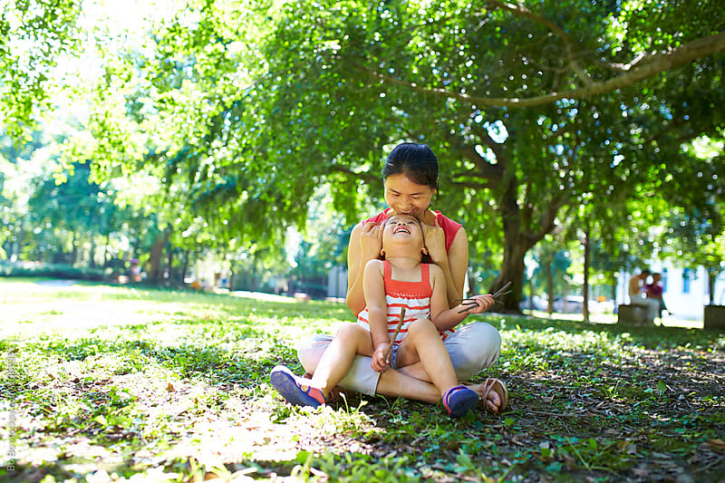 little girl sitting on her mother's leg outdoor in the park by cuiyan Liu for Stocksy United