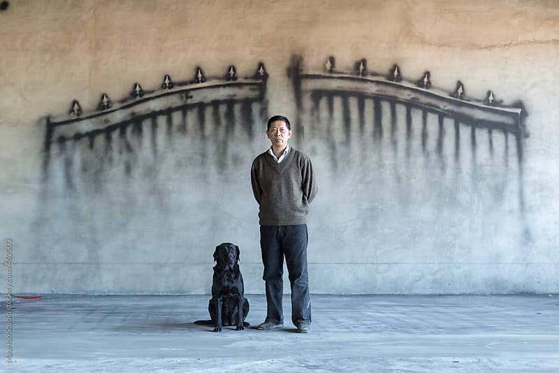 A man and dog in front of a wall with a gate painting on it by MaaHoo Studio for Stocksy United
