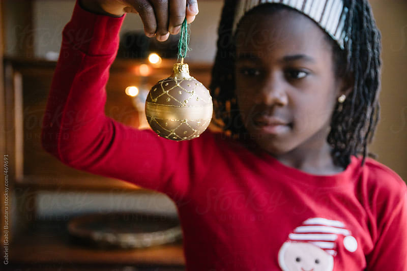 African American girl in red pajama looking at a Christmas decoration by Gabriel (Gabi) Bucataru for Stocksy United