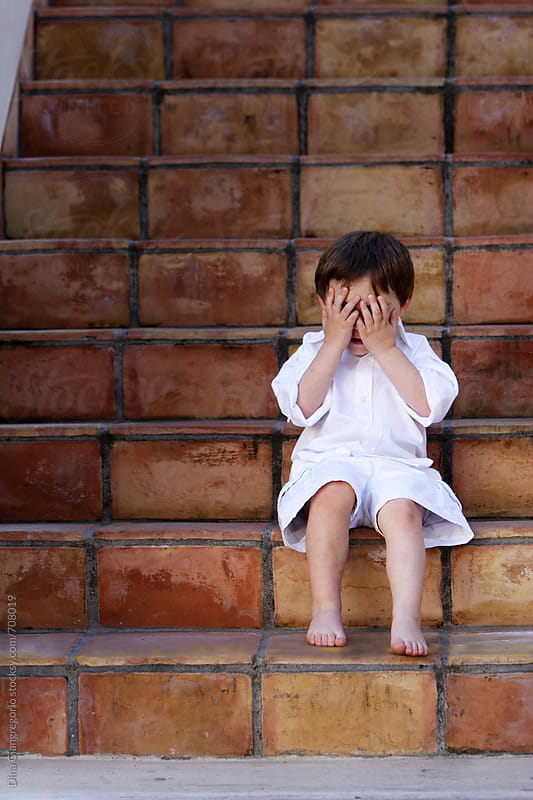 Young Boy Dressed in White Sitting on Steps Covering Eyes by Dina Giangregorio for Stocksy United