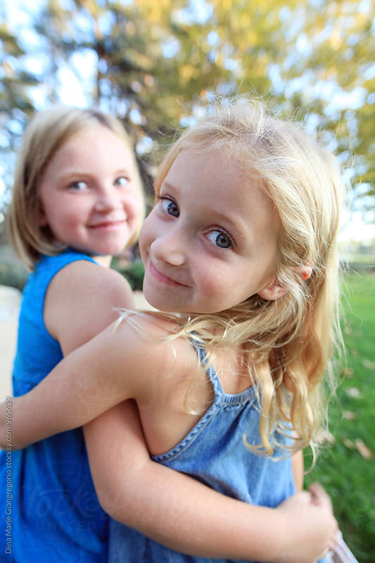 Sisters Hugging Wearing Blue One Looking Over Shoulder by Dina Giangregorio for Stocksy United