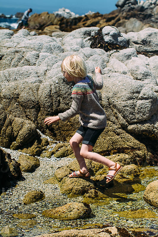 girl traversing shore at low tide by Jess Lewis for Stocksy United