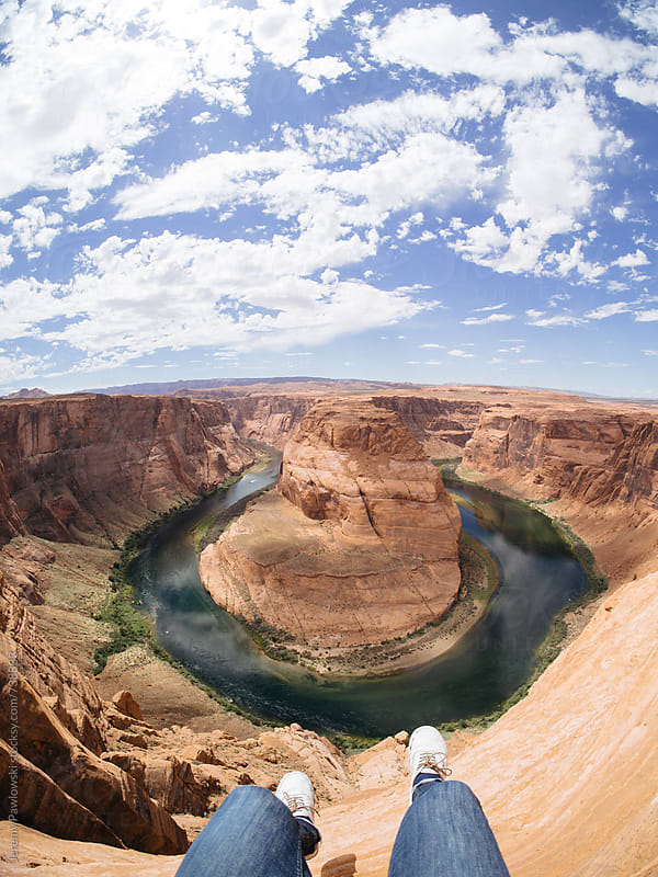 Feet danglin over Horseshoe Bend, Arizona. Sky, water and rock. by Jeremy Pawlowski for Stocksy United